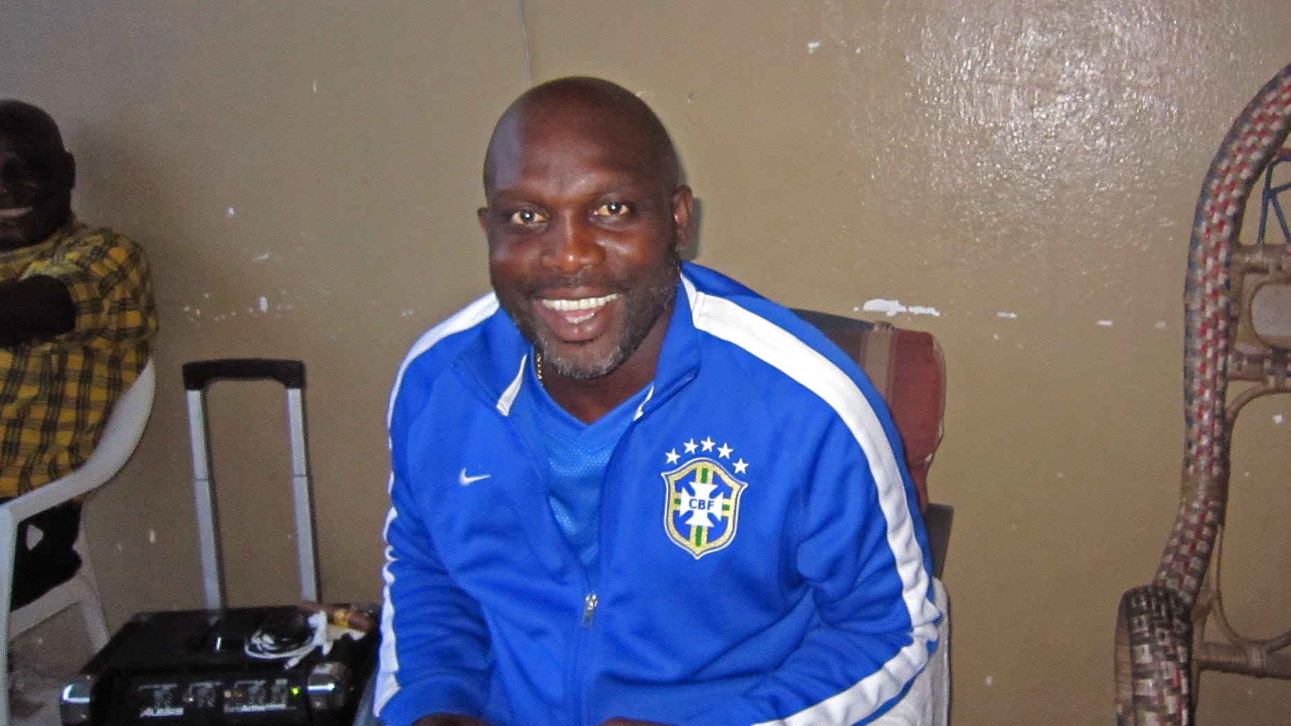 In this photo taken on Sunday, Aug. 10,  2014,  Liberian soccer star George Weah smiles inside a room in the city of  Monrovia, Liberia. Liberias world famous soccer star George Weah has produced a song to raise awareness about Ebola, the deadly disease ravaging West Africa. Weah, who before he retired was FIFAs player of the year, is now a politician and singer.(AP Photo/Jonathan Paye-Layleh)
