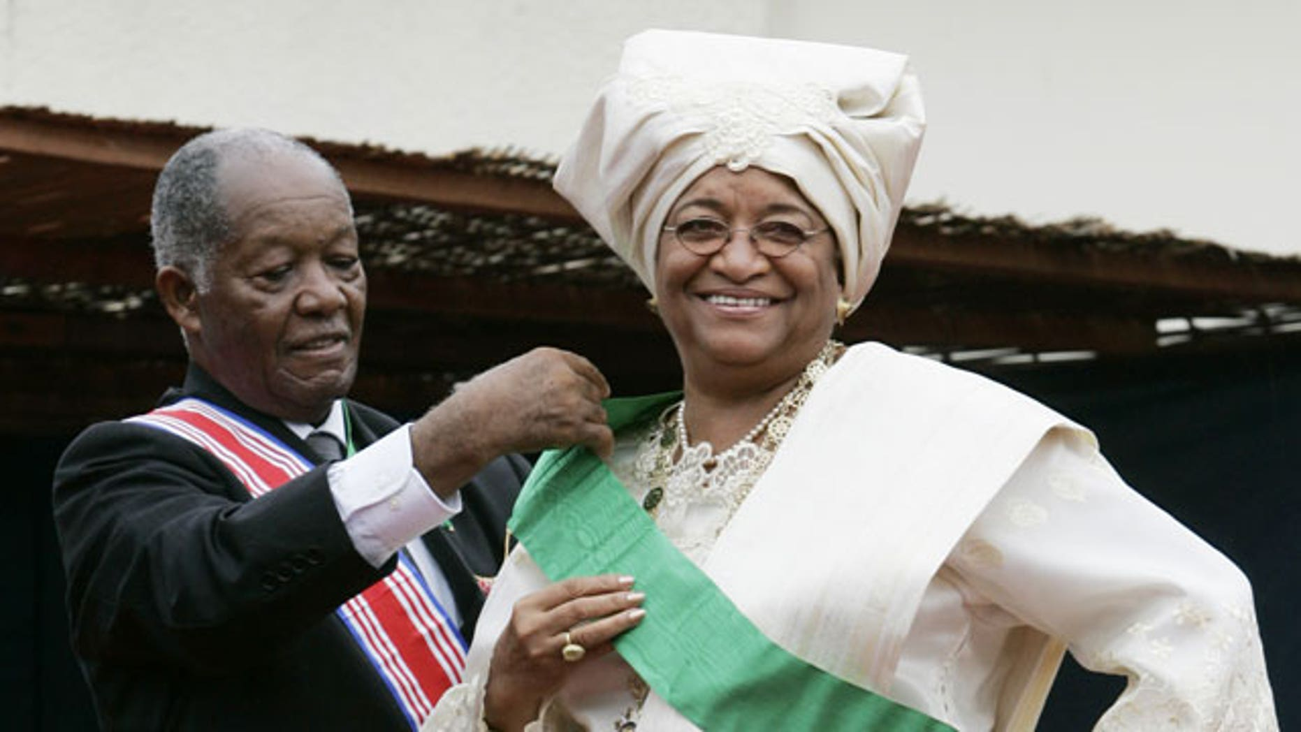 FILE - In this Jan. 16, 2006 file photo, Liberia's new President Ellen Johnson Sirleaf, right, is helped with a sash by Liberian Senior Ambassador-at-large George W. Wallace, Jr., during her inauguration at the Capitol Building in Monrovia, Liberia.