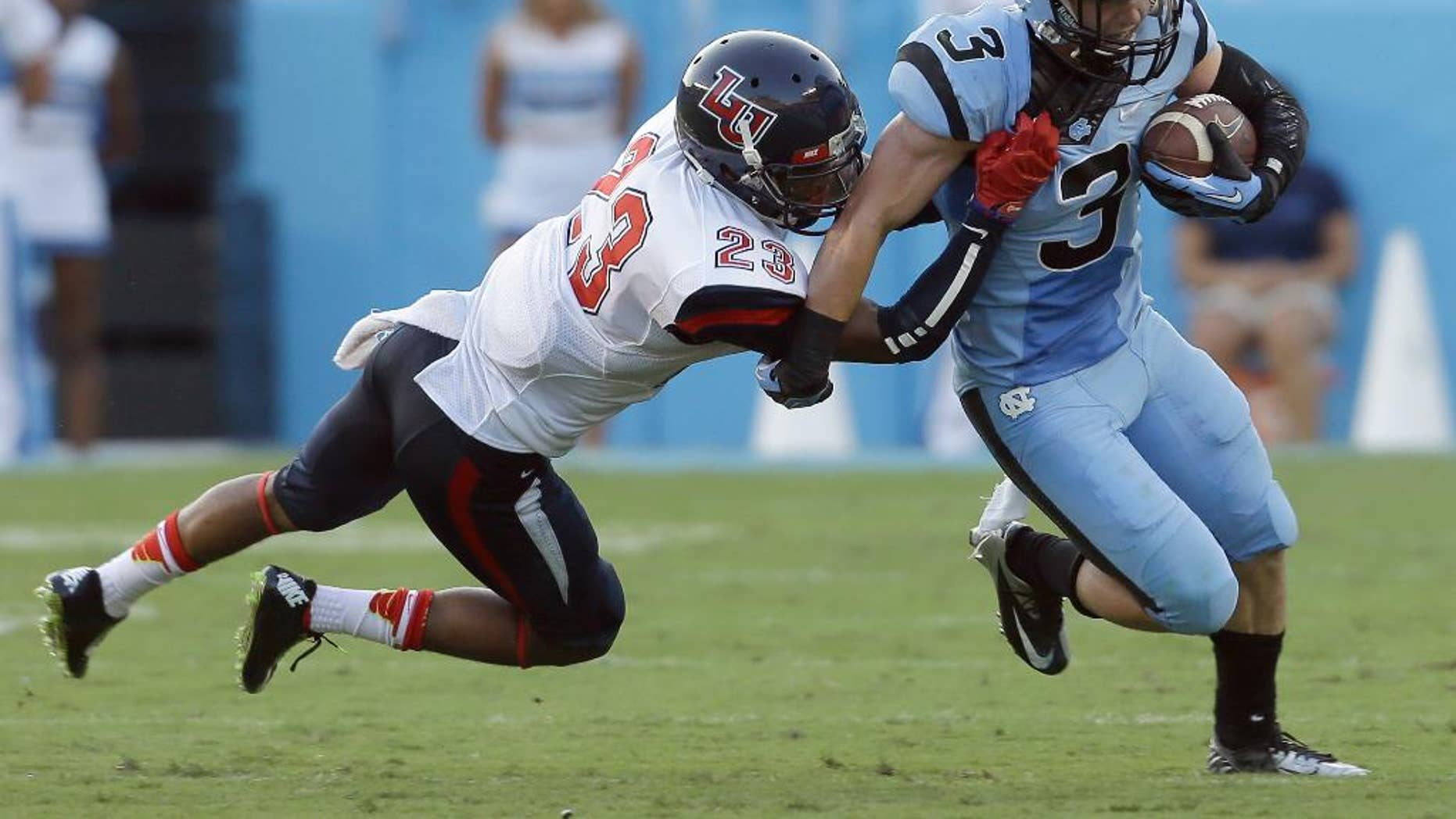 North Carolina's Ryan Switzer (3) runs the ball as Liberty's Justin Guillory (23) moves in to make the tackle during the first half of an NCAA college football game in Chapel Hill, N.C., Saturday, Aug. 30, 2014. (AP Photo/Gerry Broome)