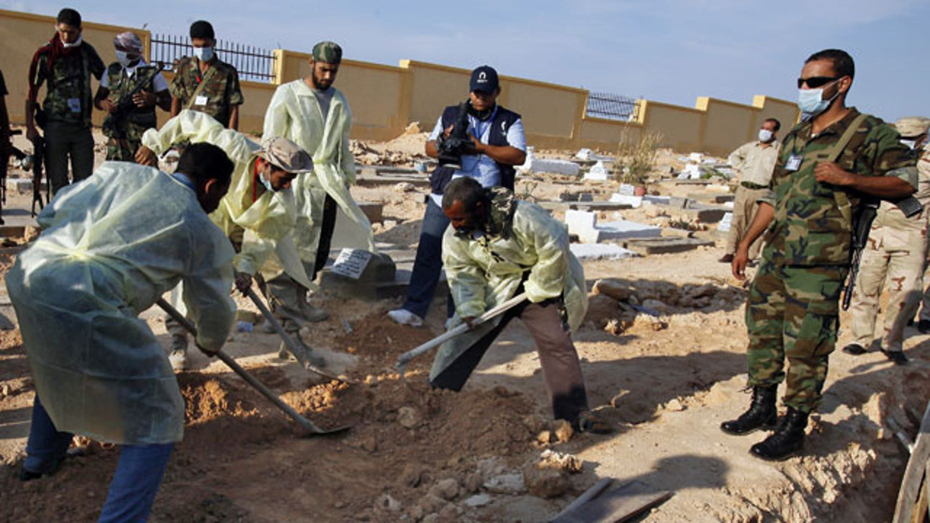 Libyan medical team and revolutionary fighters dig at a mass grave in Gargarish, on the coast some four miles, from the center of Tripoli, Libya, containing the bodies of more than 200 people who were killed in the chaos surrounding the rebel assault that ousted Muammar Qaddafi.