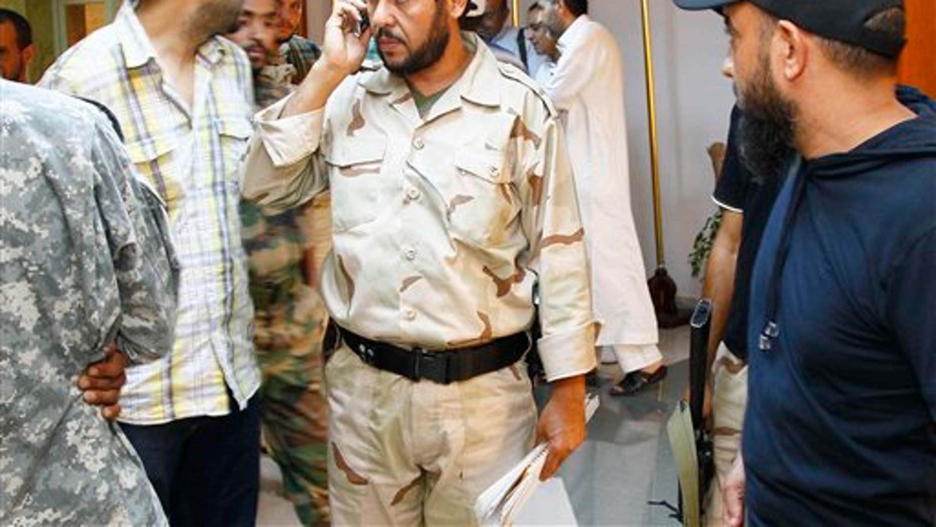 August 31: Libyan rebels' Tripoli military commander Abdel Hakim Belhaj, center, after an interview with the Associated Press in Tripoli, Libya.