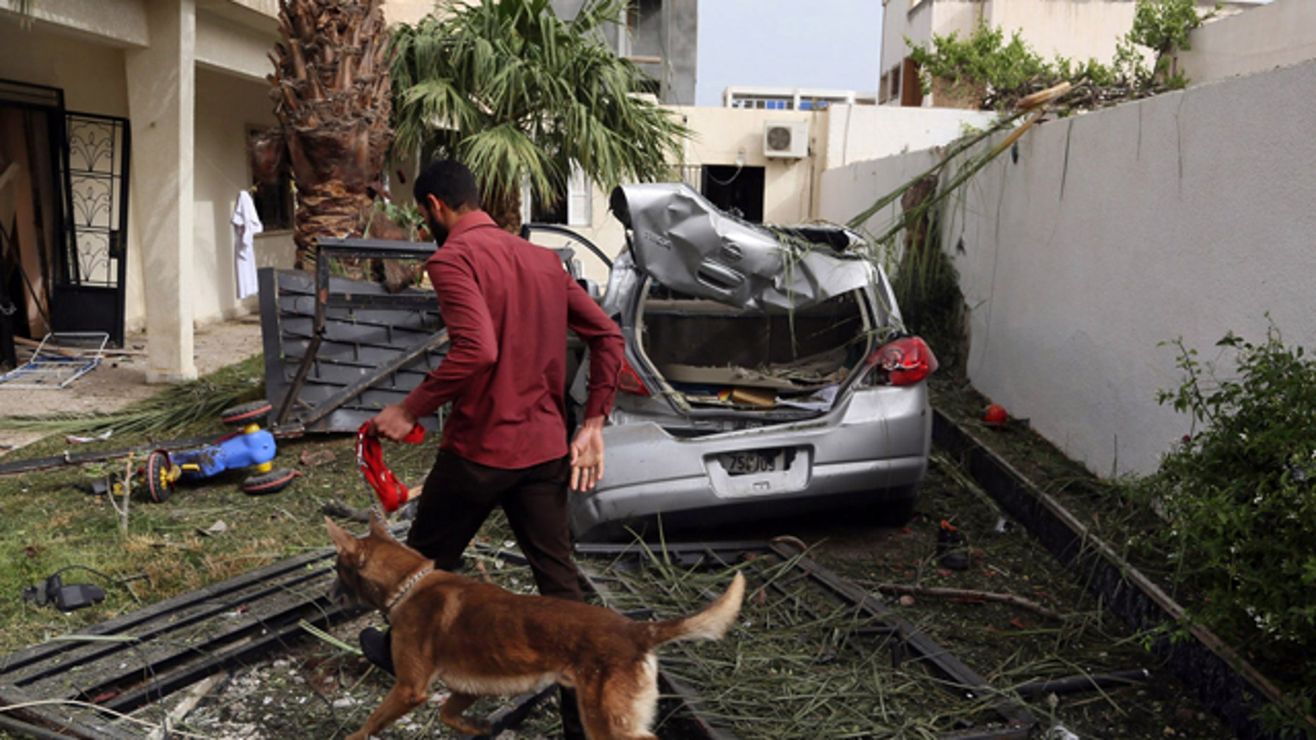 April 23, 2013: A security officer using a sniffer dog inspects the site of a car bomb that targeted the French embassy wounding two French guards and causing extensive material damage in Tripoli, Libya.