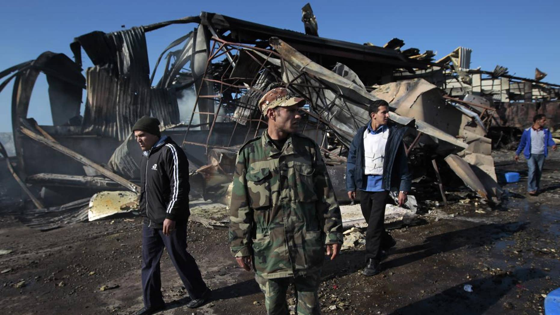 A Libyan soldier walks outside wreckage/AP Photo
