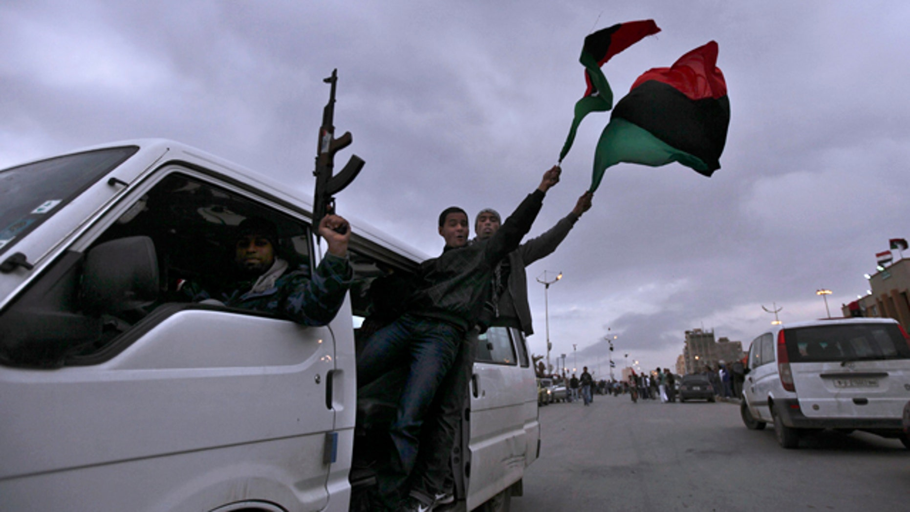 March 30: A Libyan rebel fires in air as others wave Libyan pre-Qaddafi flags as they ride a vehicle at twilight  in Benghazi, Libya.