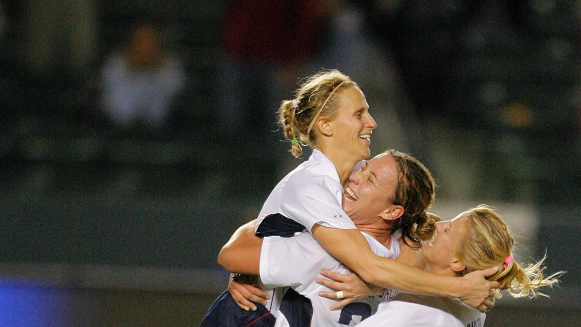 FILE - In this Nov. 26, 2006, file photo USA's Kristine Lilly, left, is congratulated by her teammates Abby Wambach, center, and Aly Wagner after Lilly made a game-winning penalty kick against Canada to win the championship in their CONCACAF Gold Cup soccer match in Carson, Calif. A day after her former team faces England in an exhibition, Lilly will be inducted into the National Soccer Hall of Fame. (AP Photo/Jae C. Hong, File)