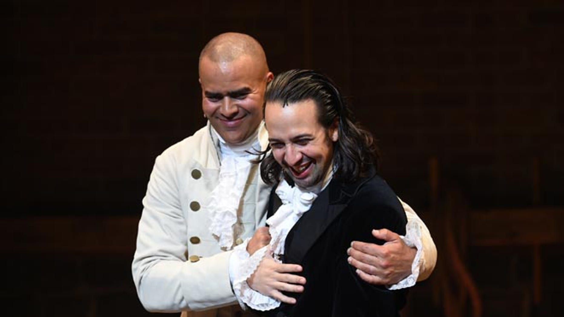 """Actor and """"Hamilton"""" creator Lin-Manuel Miranda, right, gets a hug from cast mate Christopher Jackson during his final performance curtain call at the Richard Rogers Theatre on Saturday, July 9, 2016, in New York. (Photo by Evan Agostini/Invision/AP)"""