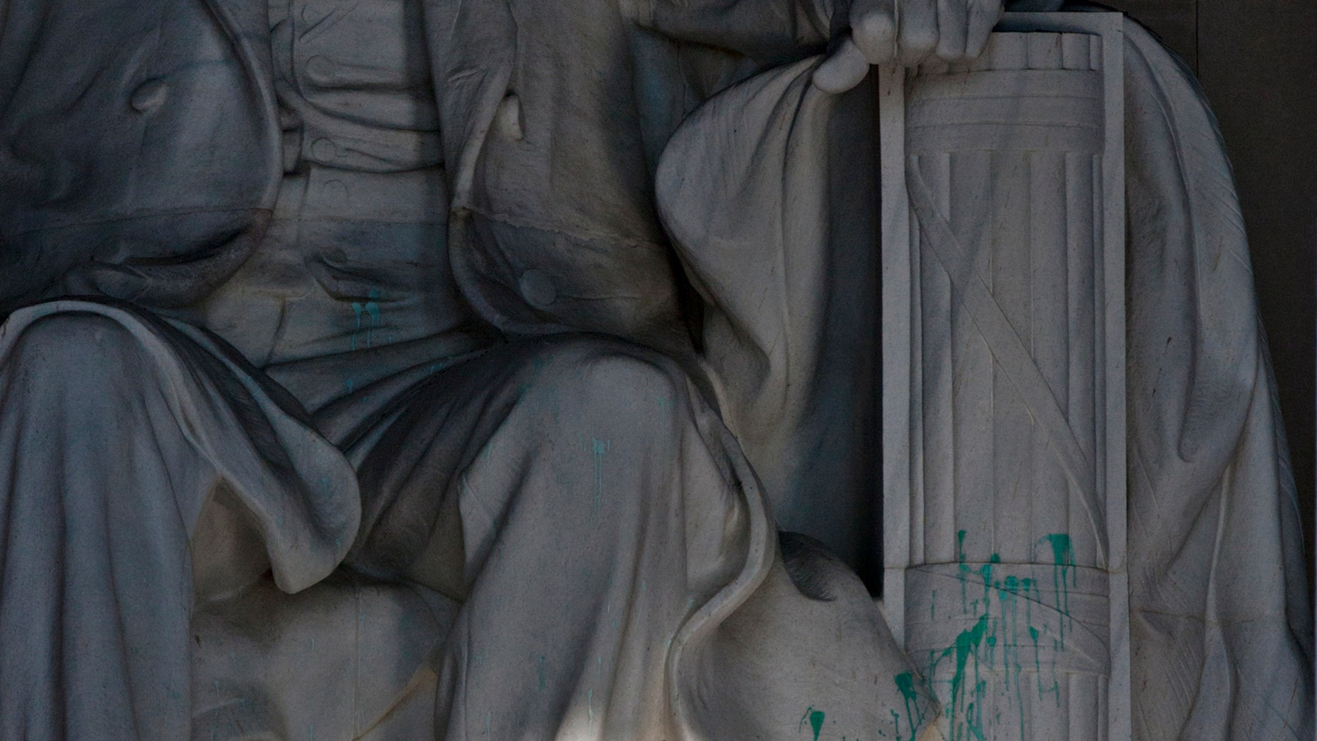 July 26, 2013: A U.S. Park Police officer stands guard next to the statue of Abraham Lincoln at the memorial in Washington after the memorial was closed to visitors after someone splattered green paint on the statue and the floor area.