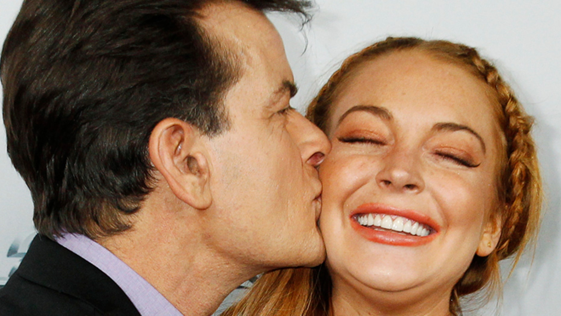 """FILE 2013: Charlie Sheen kisses co-star Lindsay Lohan on the cheek as they pose at the premiere of """"Scary Movie"""" in Hollywood."""