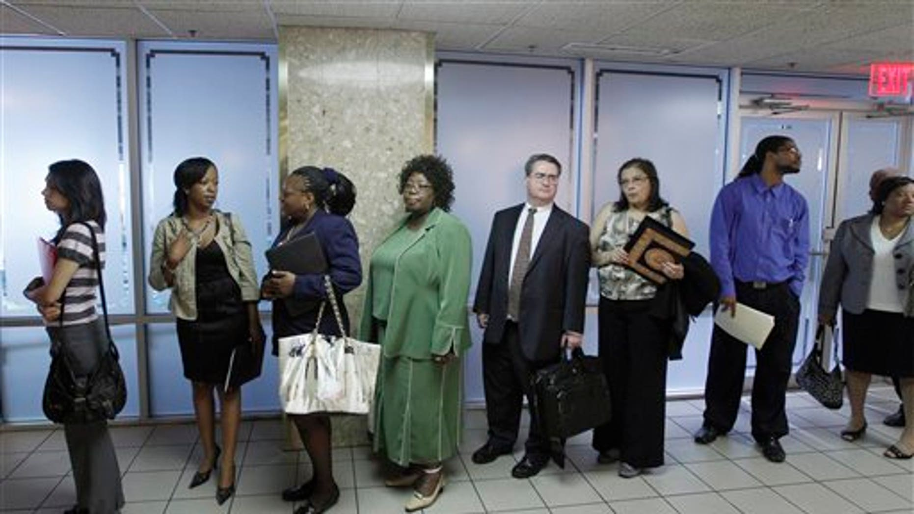 In this Aug. 4, 2011 photo, job seekers line up to register as they arrive at the Career job fair in Arlington, Va. The number of people seeking unemployment benefits decreased last week, a sign that the job market is improving slowly after a recent slump. (AP Photo/Jose Luis Magana)