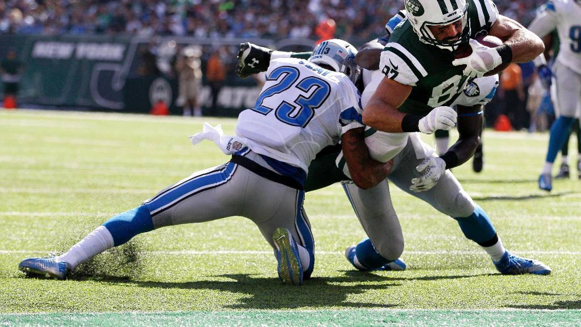 New York Jets wide receiver Eric Decker, center, dives in between Detroit Lions cornerback Darius Slay, left, and outside linebacker Tahir Whitehead for a touchdown during the second half of an NFL football game, Sunday, Sept. 28, 2014, in East Rutherford, N.J. (AP Photo/Frank Franklin II)