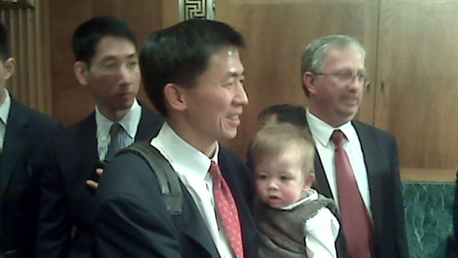 Goodwin Liu holds his son in the Senate Judiciary Committee room.  (FNC Photo/Lee Ross)