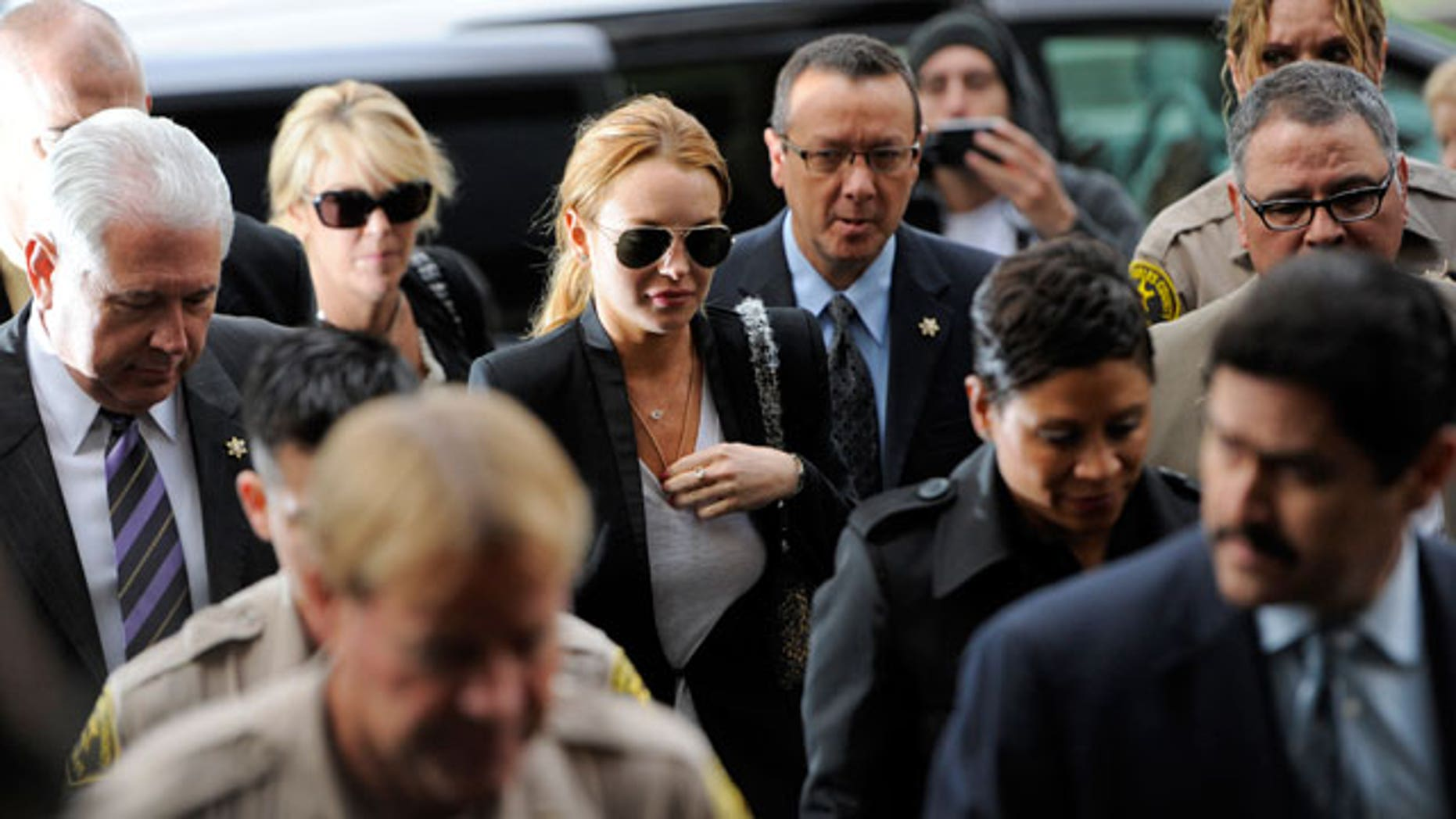 Oct. 22: Lindsay Lohan, center, arrives for a probation violation hearing at Beverly Hills Courthouse in Beverly Hills.