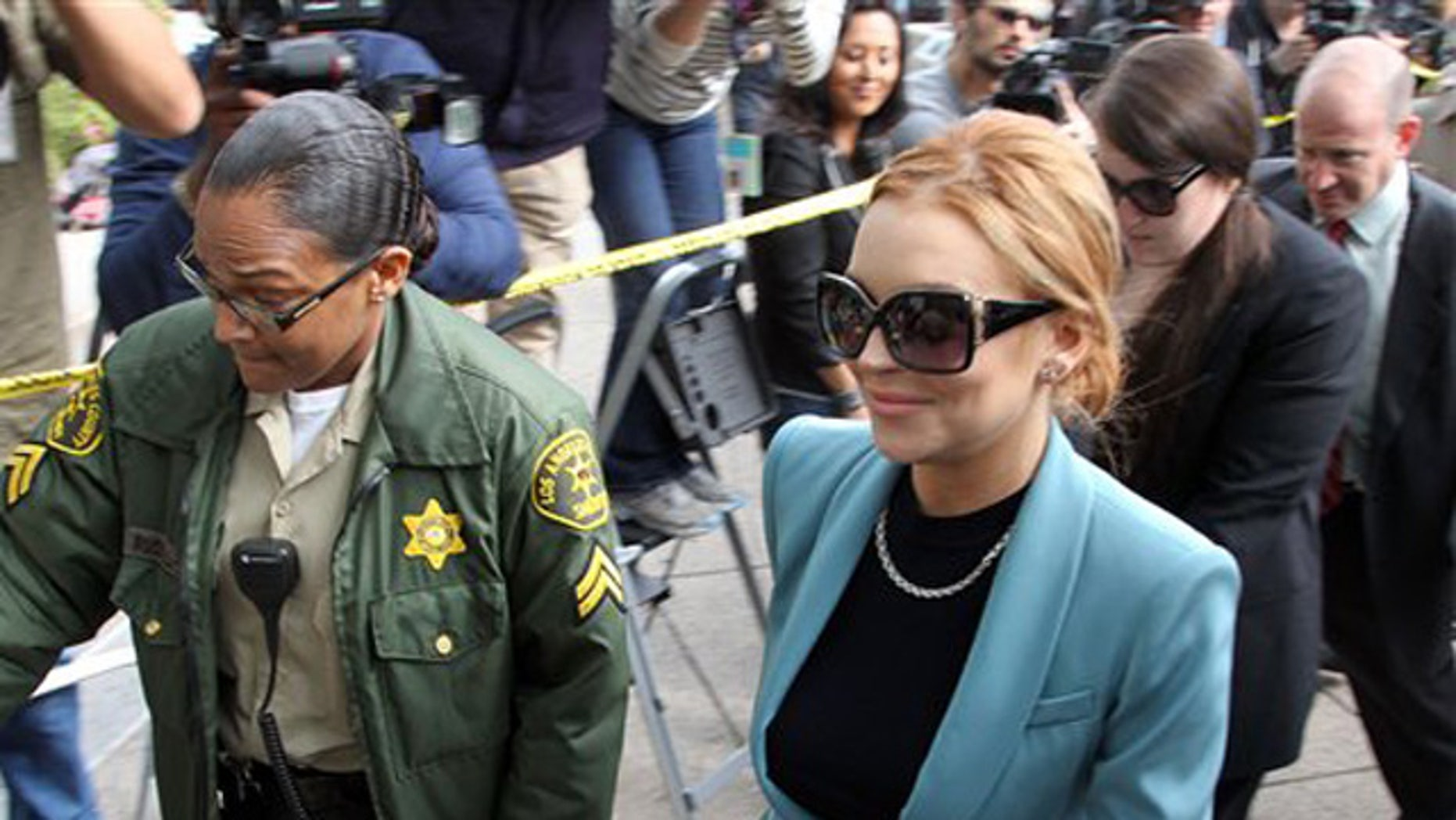Lindsay Lohan arrives for a progress report on her probation for theft charges at Los Angeles Superior Court Thursday, March 29, 2012. Lohan will update a judge on her progress on strict probation requirements that have had her doing cleanup duty at the county morgue and attending regular psychotherapy sessions since late last year. Superior Court Judge Stephanie Sautner has said she will end Lohan's probation on a 2007 drunken driving case on Thursday if she completes the requirements. (AP Photo/Reed Saxon)