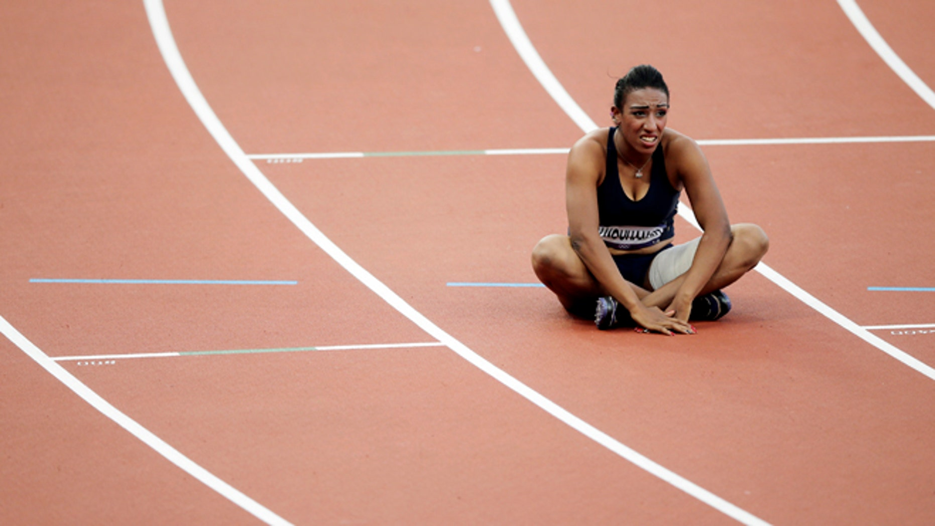 Aug. 5, 2012: Syria's Ghfran Almouhamad sits in her lane after a women's 400-meter hurdles qualifying race at the London Olympics.