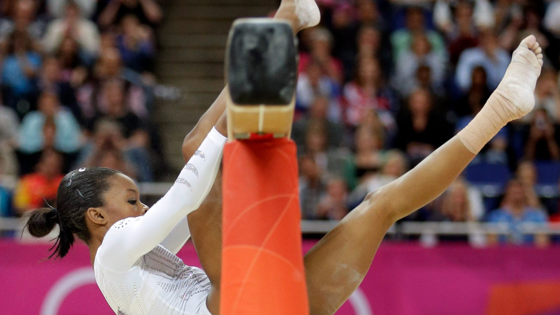 U.S. gymnast Gabrielle Douglas loses her balance and hangs onto the balance beam during the artistic gymnastics women's apparatus finals at the 2012 Summer Olympics, Tuesday, Aug. 7, 2012, in London. (AP Photo/Gregory Bull)