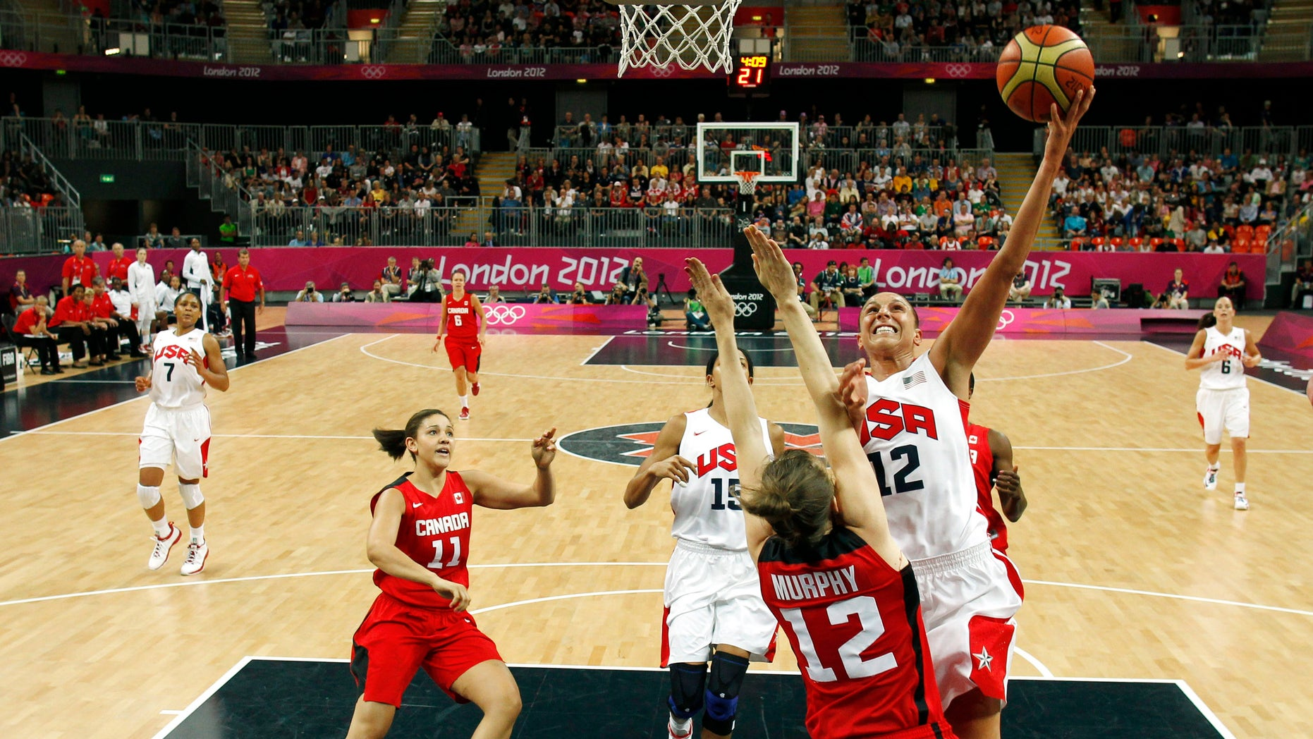 Diana Taurasi (12) of the U.S. shoots over Canada's Lizanne Murphy during a women's quarterfinal basketball match at the 2012 Summer Olympics on Tuesday, Aug. 7, 2012, in London. (AP Photo/Sergio Perez, Pool)