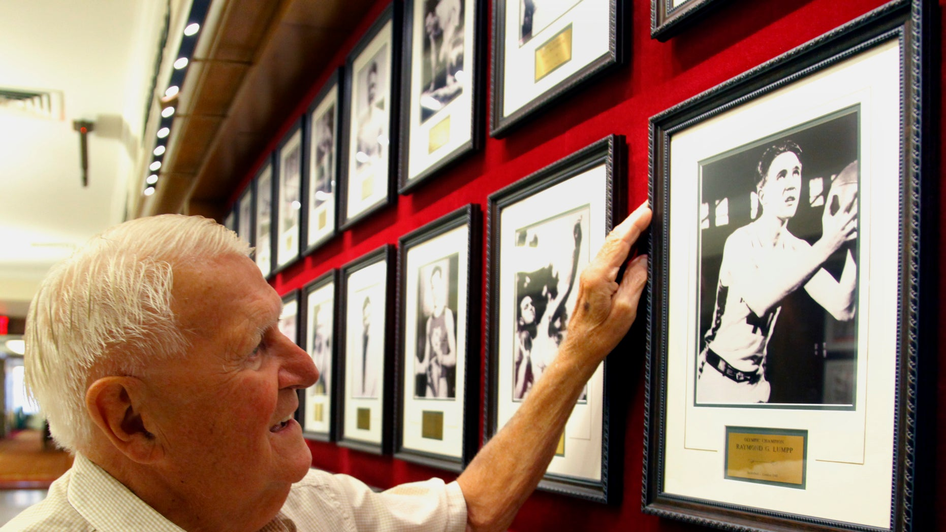 FILE - This Sept. 2, 2011 file photo shows Ray Lumpp, basketball gold medalist for the U.S. at the 1948 Olympics in London, pointing out his photo among those reserved for Olympic champions, at the New York Athletic Club. When the U.S. men's basketball team play Argentina on Friday night, the 89-year-old Lumpp promises to cheer louder than anyone else. (AP Photo/Bebeto Matthews, File)