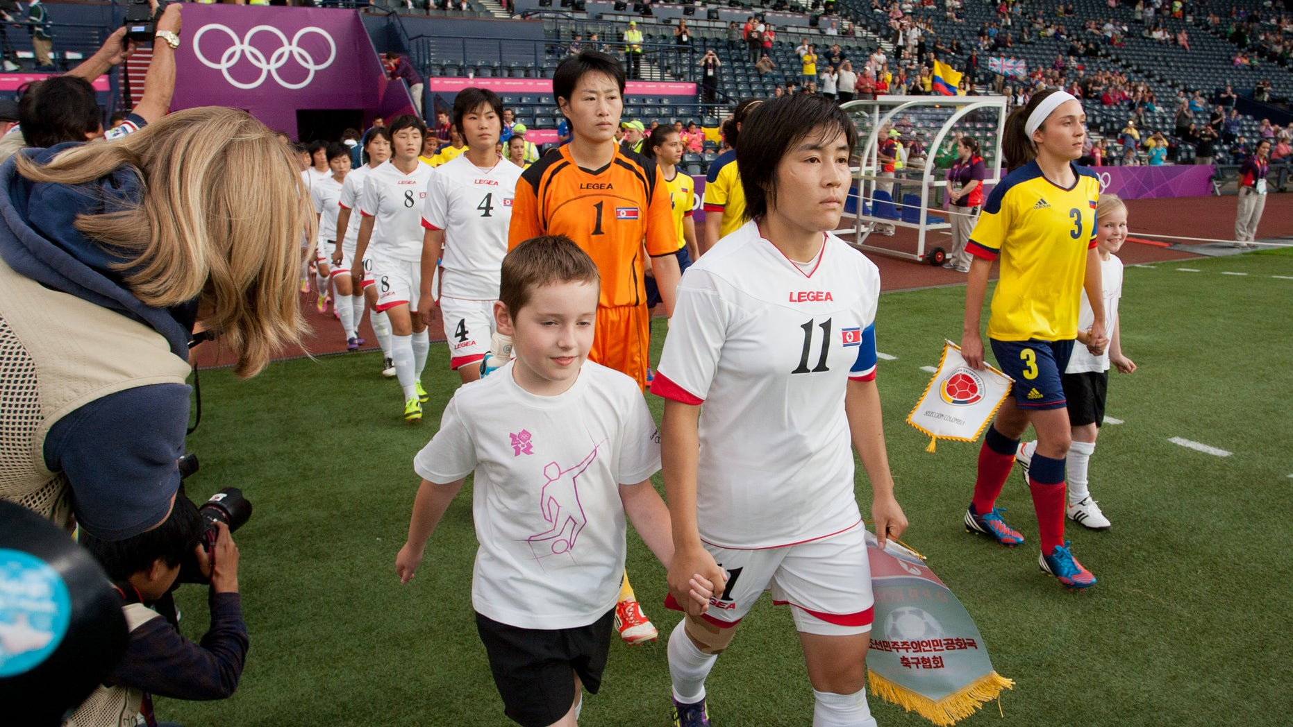 July 25, 2012: The North Korean, center, and Colombian women's soccer team walk out on to the field before their group B match, prior to the start of the London 2012 Summer Olympics at Hampden Park Stadium in Glasgow.