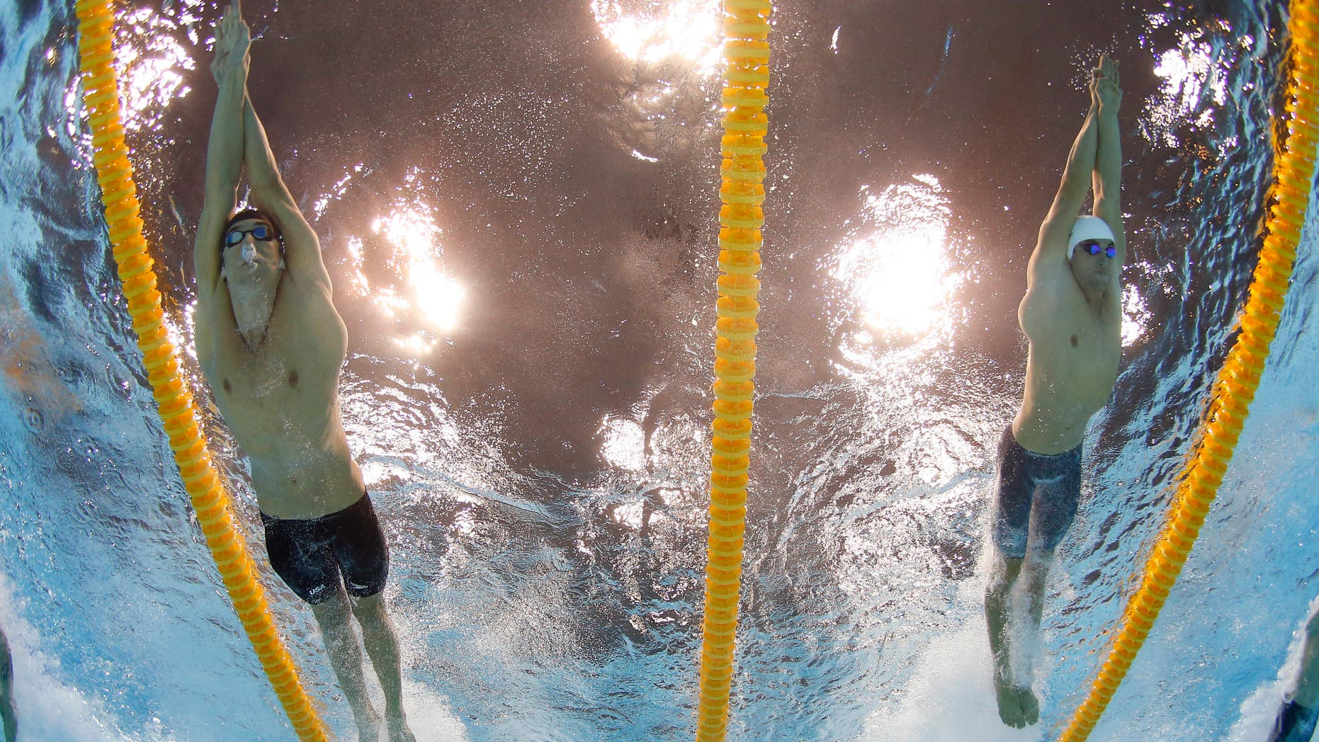July 29, 2012: United States' Michael Phelps, left, and France's Fabien Gilot compete in the men's 4x100-meter freestyle relay final at the Aquatics Centre in the Olympic Park during the 2012 Summer Olympics in London.