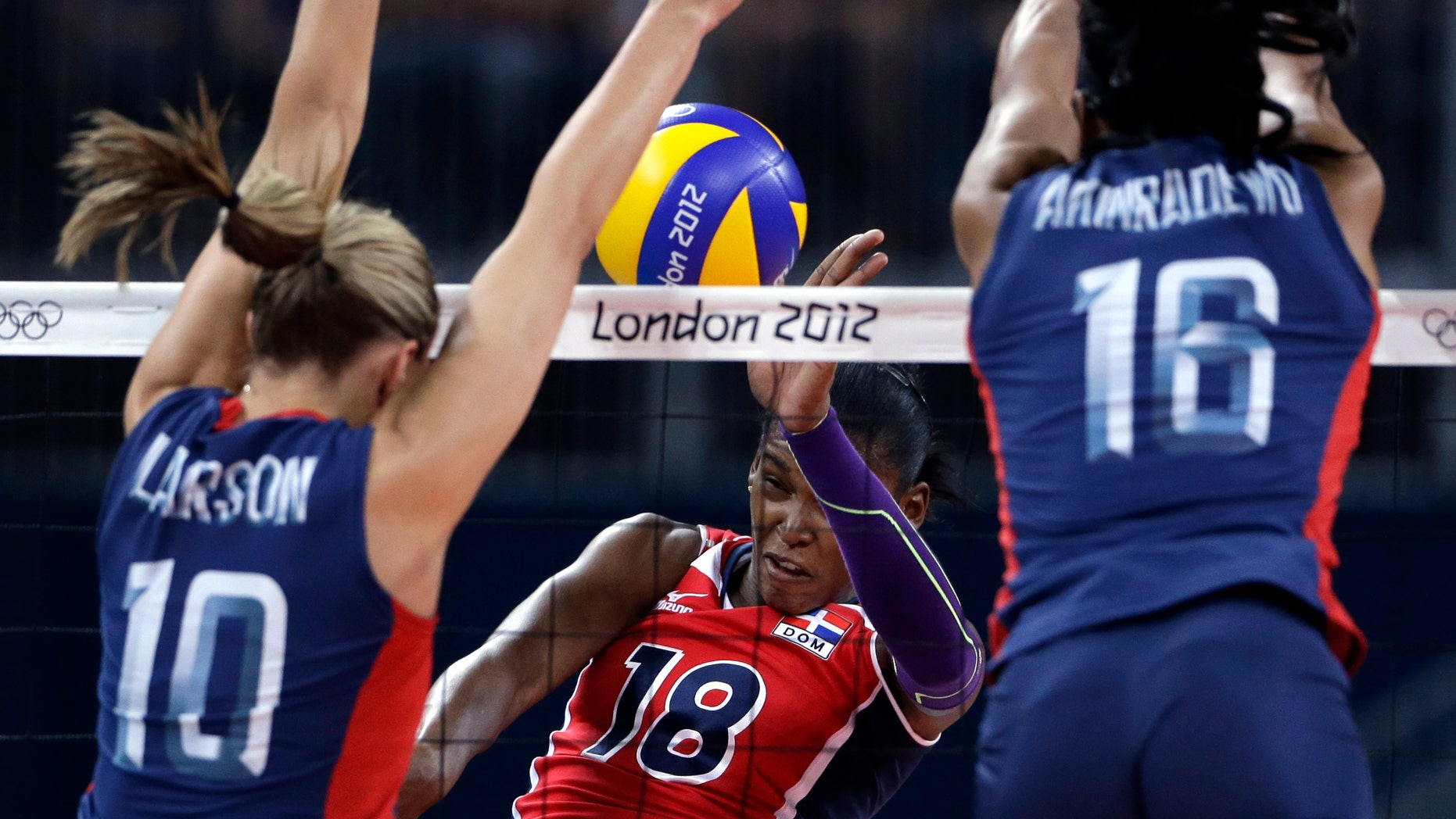 Aug. 7, 2012: United States' Jordan Larson, left, and Foluke Akinradewo, right, block a spike from Dominican Republic's Bethania de la Cruz de Pena during a women's quarterfinal volleyball match at the 2012 Summer Olympics in London.