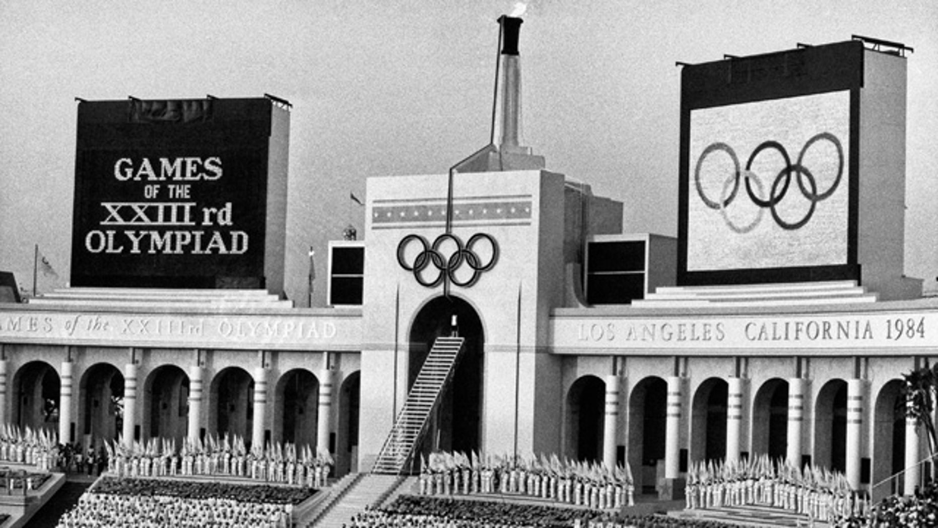 FILE - In this July 28, 1984, file photo, the Olympic flame is flanked by a scoreboard signifying the formal opening of the XXIII Olympiad after it was lit by Rafer Johnson during the opening ceremonies in the Los Angeles Memorial Coliseum. (AP Photo/Eric Risberg, File)