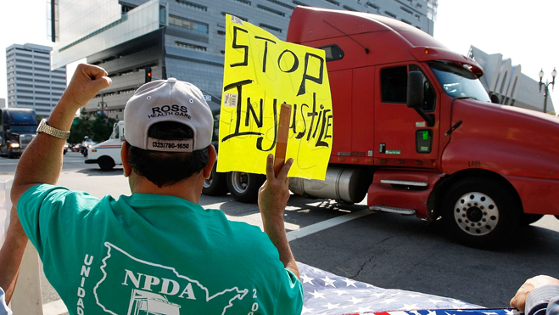 LOS ANGELES, CA - NOVEMBER 13:  A truck drives near City Hall to protest shipping container fees being assessed against independent truckers as part of the ports' Clean Truck Program to allow only newer, less-polluting trucks at the ports, on November 13, 2009 in Los Angeles, California. The members of the National Port Drivers Association, who work the ports of Los Angeles and Long Beach,  formed caravans from the ports to City Hall in downtown Los Angeles to demonstrate against the fees that they say impact their wages and hours. In October, the Port of Long Beach and the American Trucking Assn. reached a settlement over disputed elements of the air pollution cleanup plan. The port drop requirements not directly related to cleaning up the environment such as a demand for trucking companies to file financial reports, and truckers agreed to emissions, safety and security requirements. In an effort to get rid of dirty trucks, the ban on all 1988 and older trucks from the ports remains and as of January, only 2004-or-later trucks will be allowed in the port complex. Thousands of trucks make daily trips into and out of the ports of Long Beach and Los Angeles which make up the busiest seaport complex in the nation.  (Photo by David McNew/Getty Images)
