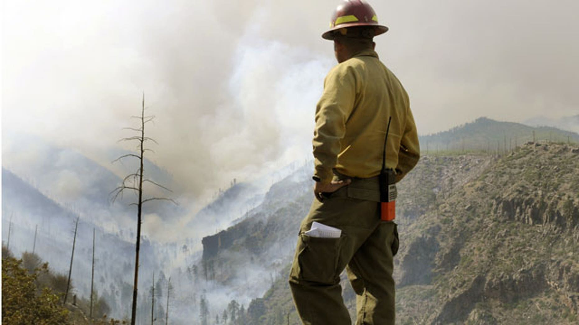 Firefighter Eugene Pino stands high above a smoke filled Los Alamos Canyon, Friday July 1, 2011 near Los Alamos, N.M.