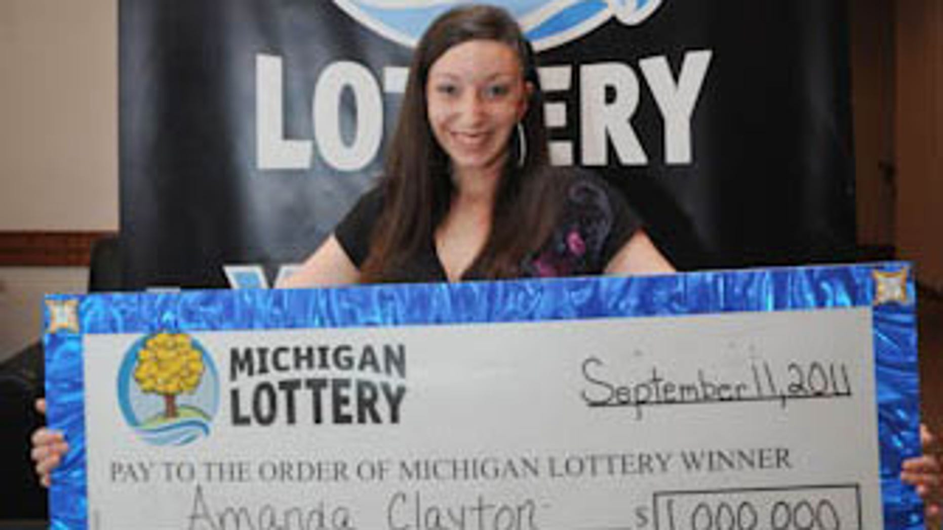 March 8: Photo provided by the Michigan Lottery, Amanda Clayton holds her $1 million lottery check. Clayton, who continued to get food stamps after winning a $1 million lottery jackpot, has been charged with welfare fraud.