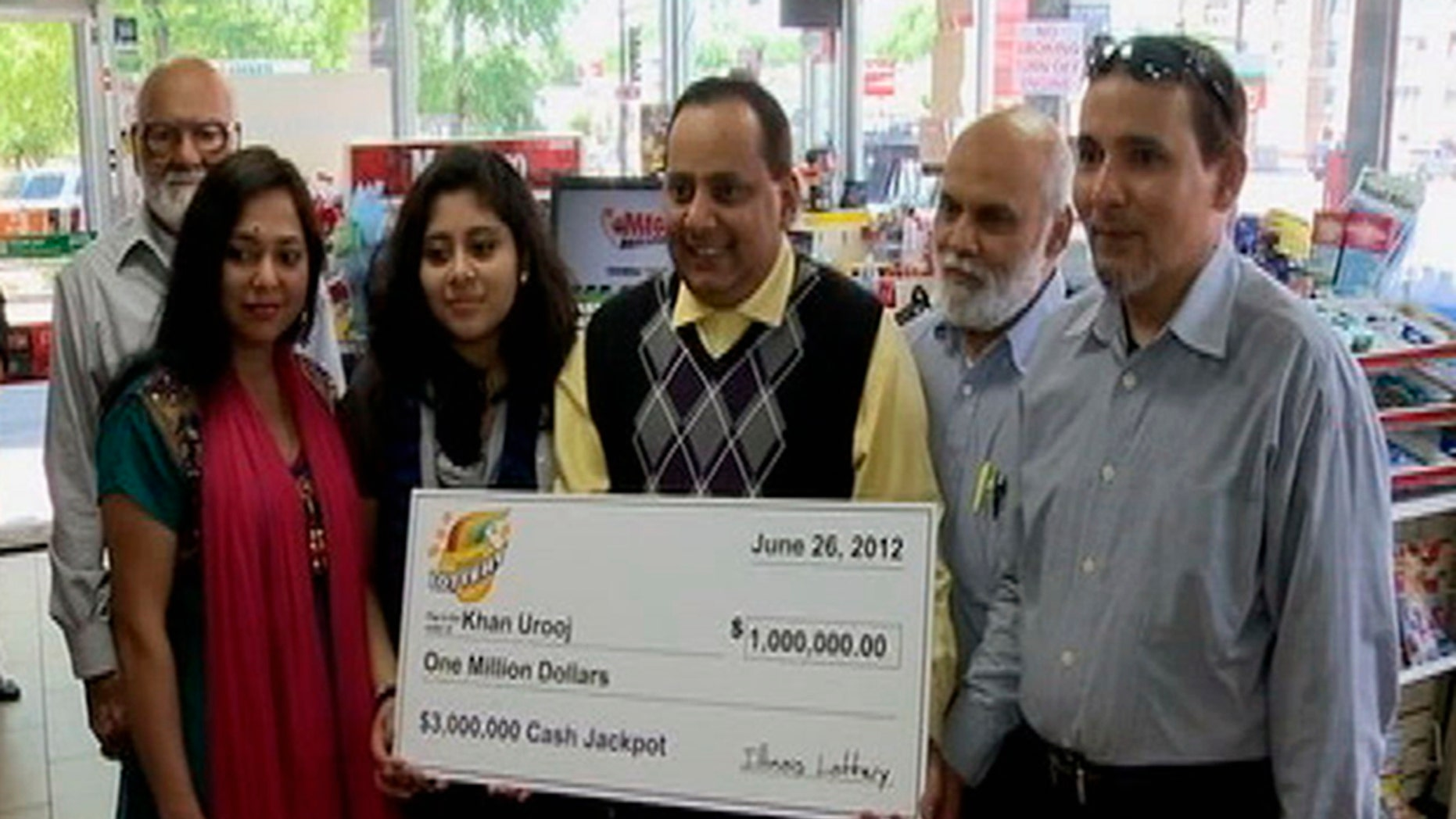 June 2012: This photo provided by WMAQ-TV in Chicago shows Urooj Khan, center, holding a ceremonial check in Chicago for $1 million as winner of an Illinois instant lottery game.