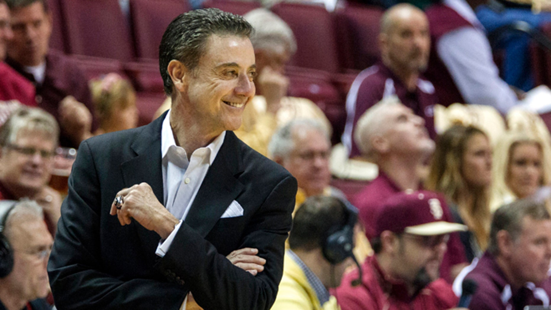 Louisville head coach Rick Pitino smiles at a referee after receiving a warning in the first half of an NCAA college basketball game against Florida State, Saturday, Feb. 28, 2015,  in Tallahassee, Fla. (AP Photo/Mark Wallheiser)