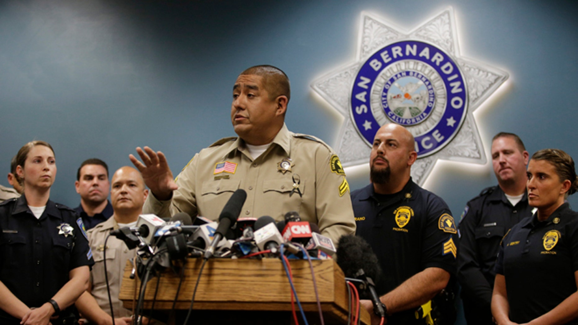 "San Bernardino County Sheriff's detective Jorge Lozano, center, answers questions from reporters during a news conference with the first responders on the scene of last week's shooting, Tuesday, Dec. 8, 2015, in San Bernardino, Calif. Lozano was captured on video in a hallway of the Inland Regional Center telling employees and others who were stranded to follow him and that he would ""take a bullet before you do."" (AP Photo/Jae C. Hong)"