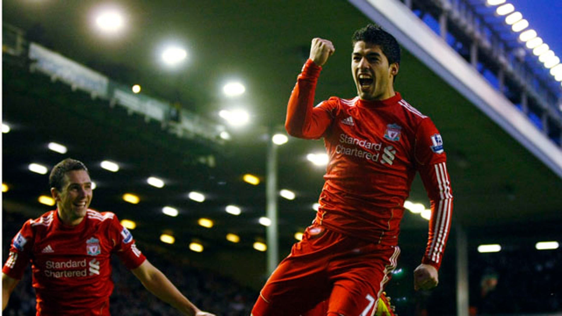 Liverpool's Luis Suarez, right, celebrates with teammate Stewart Downing after scoring a goal against Queens Park Rangers during their English Premier League soccer match at Anfield, Liverpool, England, Saturday Dec. 10, 2011. (AP Photo/Tim Hales)