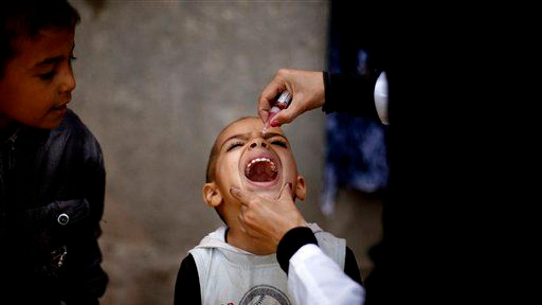 This 2014 file photo shows a Yemeni health worker giving a boy a polio vaccine during a house-to-house polio immunization campaign in Sanaa.