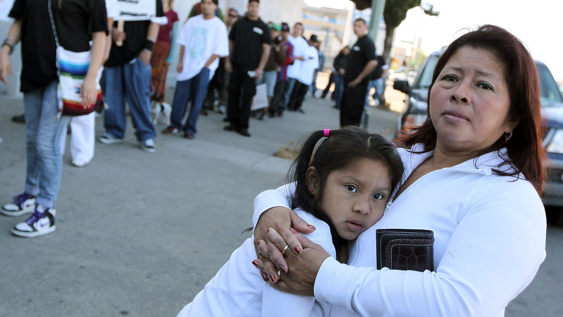 """OAKLAND, CA - APRIL 30:  A woman embraces her child as they watch the group """"Youth United For Justice"""" protest Arizona's new immigration law April 30, 2010 in Oakland, California. Dozens of people marched in protest of Arizona state bill 1070 which was signed into law this past week and gives law enforcement officials unprecedented authority to stop and question  suspected illegal immigrants.  (Photo by Justin Sullivan/Getty Images)"""
