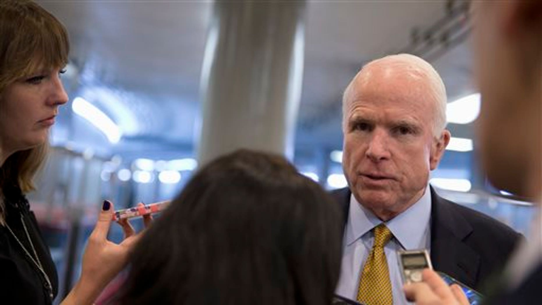 In this Oct. 20, 2015, photo, Senate Armed Service Committee Chairman Sen. John McCain, R-Ariz., talks to reporters near the subway on Capitol Hill in Washington. In the fight against the Islamic State group, members of Congress talk tough on extremism, but most want nothing to do with voting to legally authorize the military campaign, preferring to let the president take ownership of the mission. (AP Photo/Carolyn Kaster)
