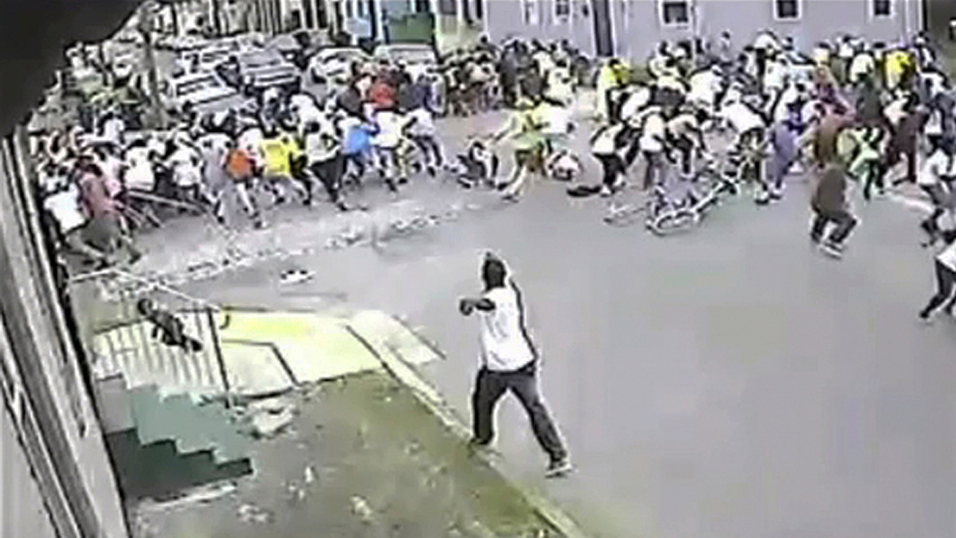 May 12, 2013: A man in a white shirt, bottom center, shoots into a crowd of people, on Mother's Day in New Orleans. New Orleans officials and cultural advocates say the Mothers Day parade shootings that left 20 people injured won't spell the end of second-line parades.