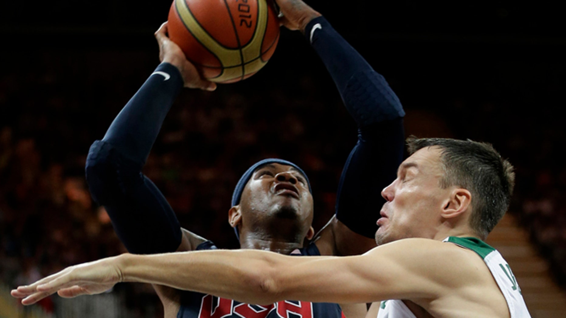 Aug. 4, 2012: USA's Carmelo Anthony is defended by Lithuania's Sarunas Jasikevicius, right, during a preliminary men's basketball game at the 2012 Summer Olympics in London.