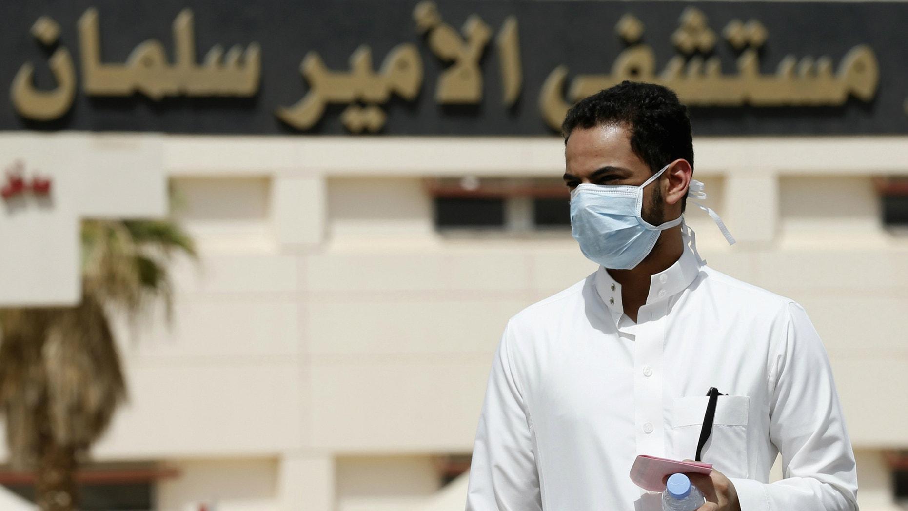 A man wearing a mask walks outside Prince Salman bin Abdulaziz hospital, in Riyadh.