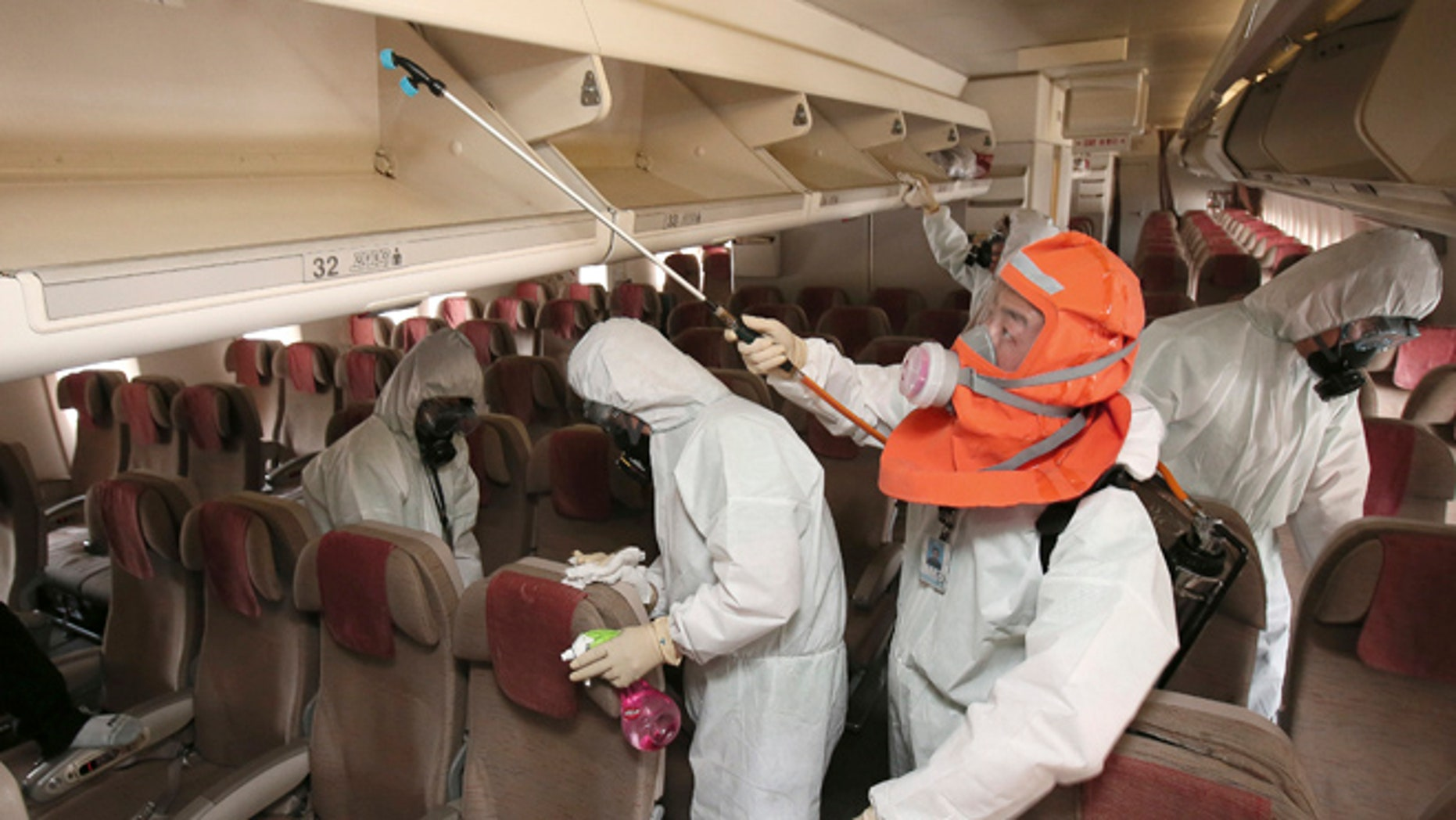 June 4, 2015: Workers wearing protective gears spray anti-septic solution in an airplane amid rising public concerns over the spread of MERS virus at Incheon International Airport in Incheon, South Korea.