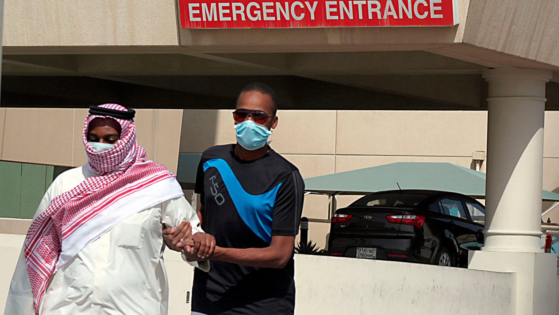 A man, wearing a surgical mask as a precautionary measure against the novel coronavirus, helps a friend who has the common flu near a hospital in Khobar city in Dammam May 23, 2013.