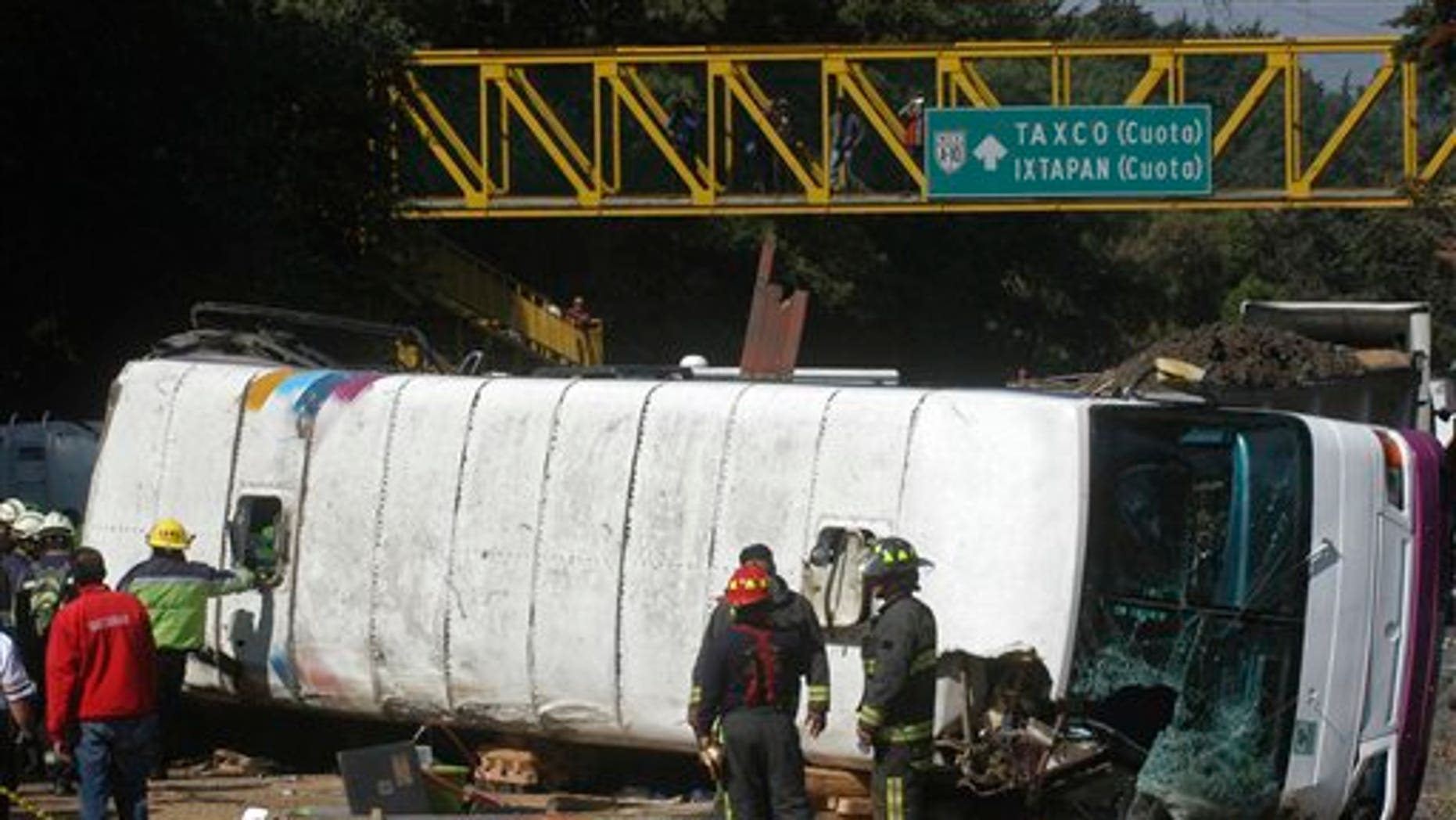 April 12, 2012: Emergency responders stand next to a passenger bus that was struck by a cargo truck in a highway on the outskirts of Mexico City, on Thursday. The bus was carrying students from the National Autonomous University of Mexico (UNAM) headed to do field studies. At least 6 students and one professor were killed.
