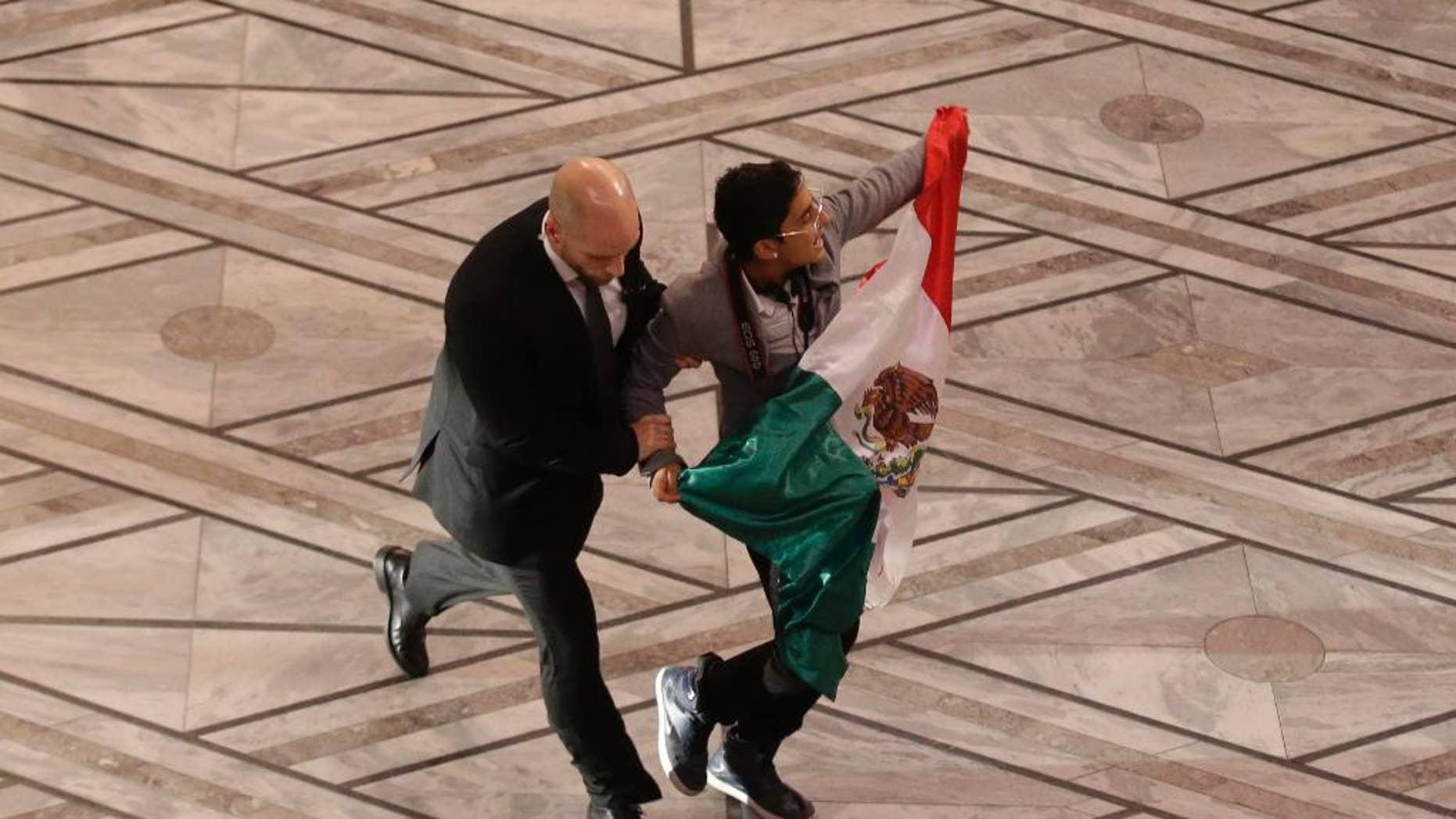 Un agente de seguridad retira a un hombre con una bandera mexicana luego de su intento de subir al escenario con los ganadores del premio Nobel de la Paz, la paquistaní Malala Yousafzai y el indio Kailash Satvarthi, en la ceremonia anual en Oslo, Noruega, el miércoles 10 de diciembre de 2014. El mexicano es un estudiante que lo hizo en protesta por la desaparición de 43 normalistas hace más de dos meses en el sur de México, según un familiar. Adán Cortés Salas, de 21 años, fue detenido por la policía noruega. (AP Foto/Matt Dunham)