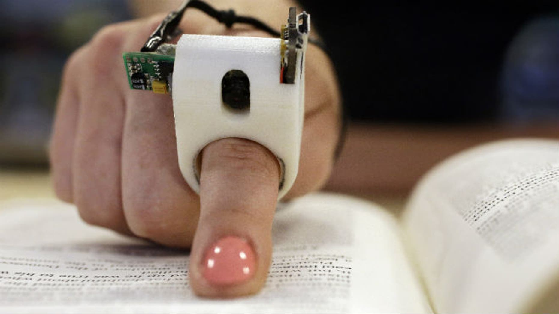 A model wears a FingerReader ring at the Massachusetts Institute of Technology's Media Lab in Cambridge, Mass. (AP Photo Stephan Savoia)