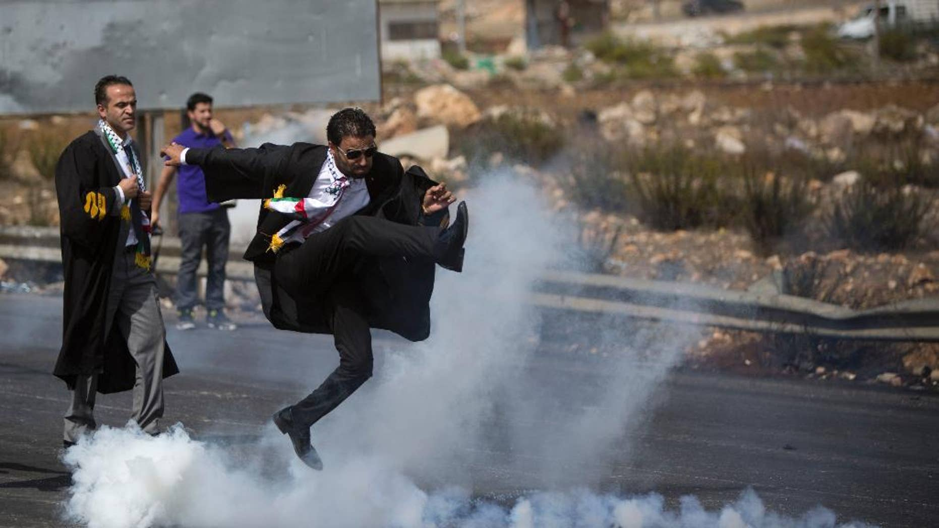 Oct. 12, 2015: lawyer wearing his official robes kicks a tear gas canister back toward Israeli soldiers during a demonstration by scores of Palestinian lawyers.
