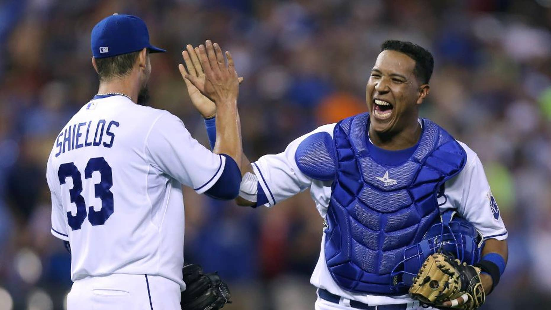 FILE - In this Aug. 9, 2014, file photo, Kansas City Royals  catcher Salvador Perez celebrates with starting pitcher James Shields (33) after Shields threw a complete game shutout against the San Francisco Giants in Kansas City, Mo. After making the most starts behind the plate of any big league catcher in a century, Salvador Perez wants more. The Kansas City Royals star was among 29 players on the roster announced Friday, Nov. 7, 2014,  for the Major League Baseball all-star postseason tour of Japan.  (AP Photo/Ed Zurga, File)