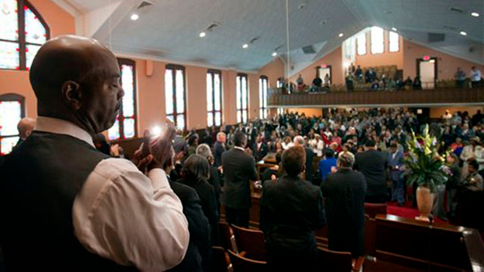 Choir member Kevin Sykes, left, applauds during a ceremony to mark the restoration of the sanctuary of the historic Ebenezer Baptist Church where Dr. Martin Luther King Jr. preached Friday, April 15, 2011 in Atlanta. (AP Photo/David Goldman)
