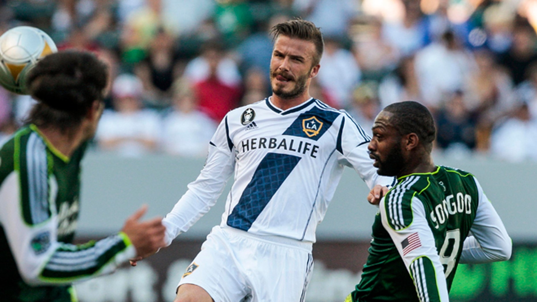 June 17, 2012: Los Angeles Galaxy midfielder David Beckham, center, makes a pass around Portland Timbers midfielder Franck Songo'o, right, as Portland Timbers defender Mike Chabala, left, gives chase during the first half of an MLS soccer match in Carson, Calif.