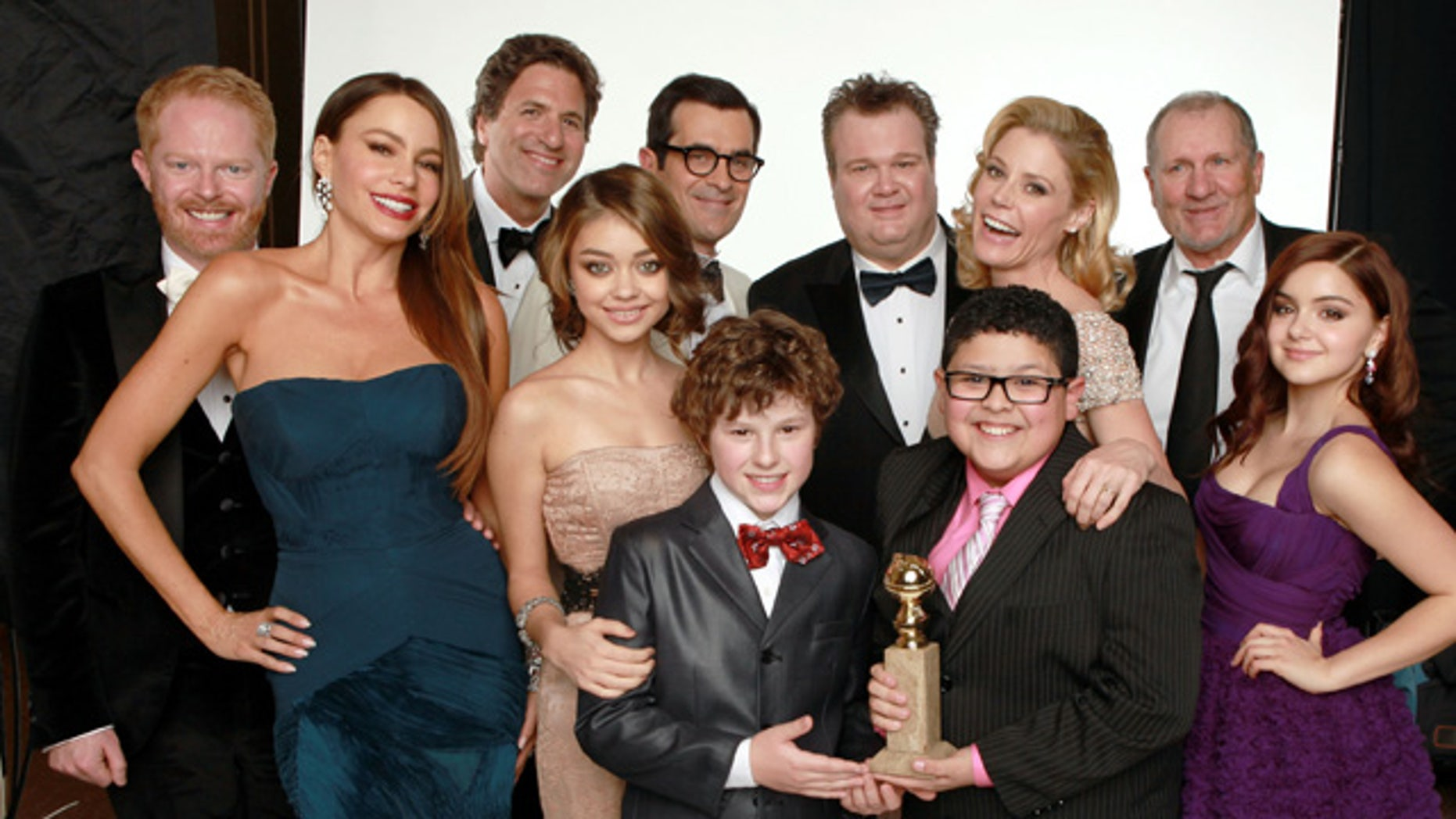 """BEVERLY HILLS, CA - JANUARY 15:  (L-R) Actors Jesse Tyler Ferguson, Sofia Vergara, creator/producer Steven Levitan, actors Sarah Hyland, Ty Burrell, Nolan Gould, Eric Stonestreet, Julie Bowen, Rico Rodriguez, Ed O'Neill and Ariel Winter, winners of the Best Television Series - Musical or Comedy award for """"Modern Family"""" pose for a portrait backstage at the 69th Annual Golden Globe Awards held at the Beverly Hilton Hotel on January 15, 2012 in Beverly Hills, California.  (Photo by Christopher Polk/Getty Images)"""