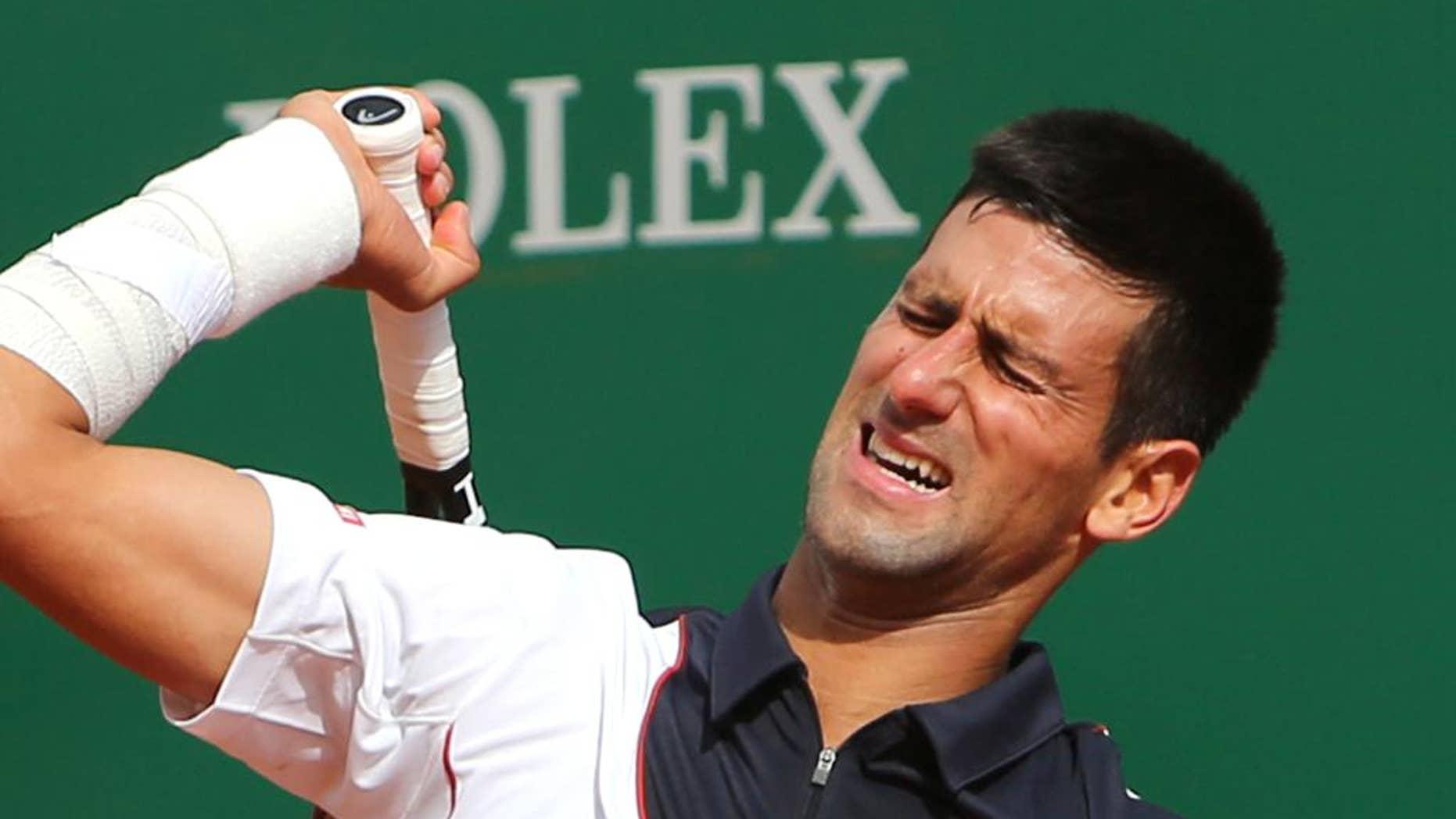 Novak Djokovic reacciona después de perder un punto frente a Roger Federer en semifinales del Masters de Montecarlo el 19 de abril del 2014. (AP Foto/Claude Paris)
