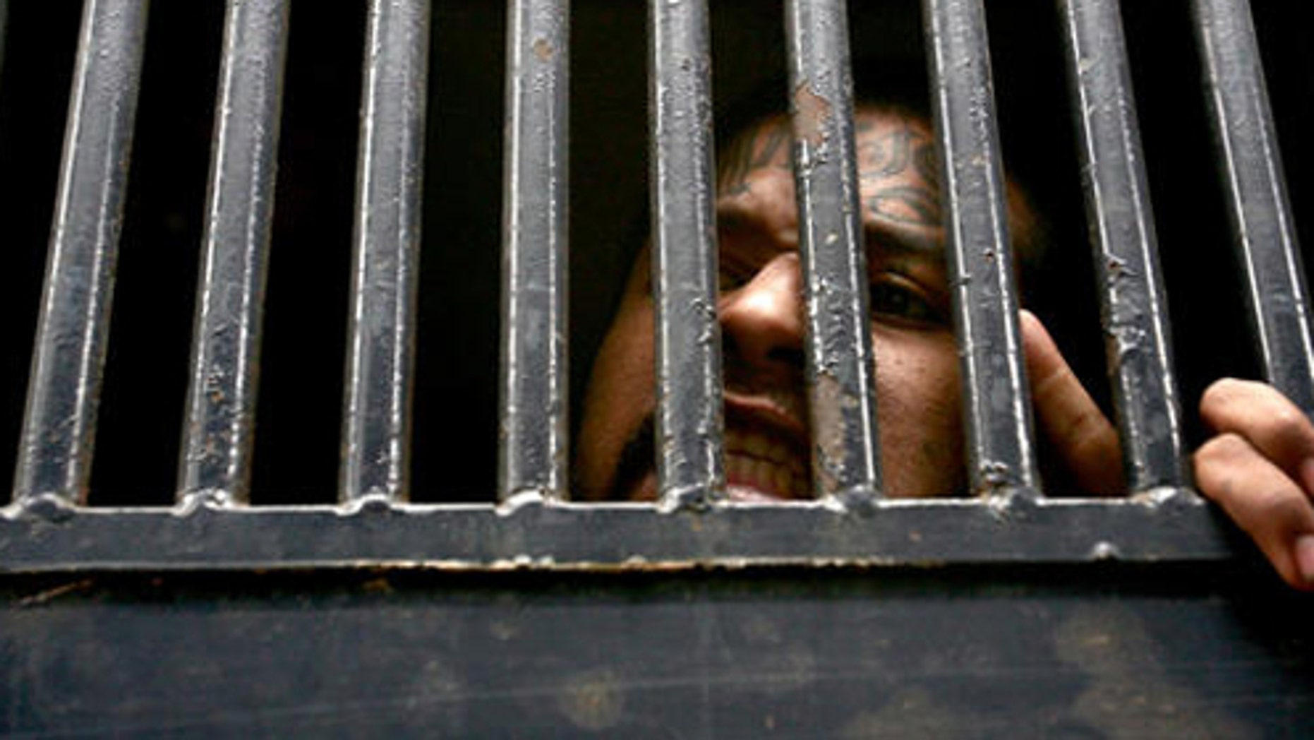 ** ALTERNATIVE CROP OF ABD106 ** A member of the 'Mara Salvatrucha' gang, reacts from  inside of a  prison bus as he is taken away to be separated from the rest of the prisoners after a riot in the Pavoncito penitentiary, in Fraijanes, Guatemala, Tuesday, March 27, 2007. The prisoners refused to coexist with another group of prisoners, allegedly participants of the murder of the four policemen accused of killing the Salvadoran congressmen last month. (AP Photo/Rodrigo Abd)